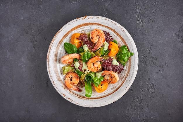 Insalata fatta in casa con gamberi fritti, pomodori gialli, rucola, spinaci, lattuga e salsa su una ciotola di ceramica