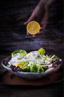 Insalata fatta in casa con lattuga, ravanello, cipolla bianca, uova sode e formaggio feta, mano che tiene un limone