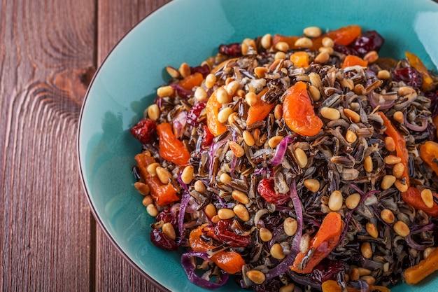 Insalata fatta in casa con riso selvatico, frutta secca e pinoli.