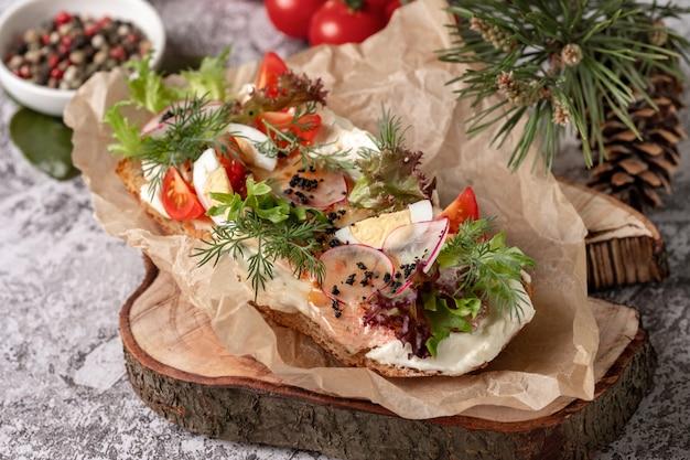 Panino fatto in casa con prosciutto, cetriolo, germogli di ravanello su tavola di legno, vista dall'alto