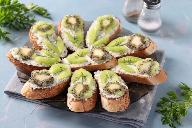 Panini fatti in casa con kiwi, crema di formaggio e aglio su un piatto su superficie azzurra