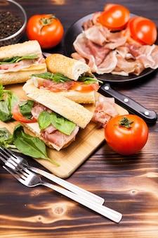 Panini fatti in casa su una tavola di legno circondati dagli ingredienti di cui era fatto
