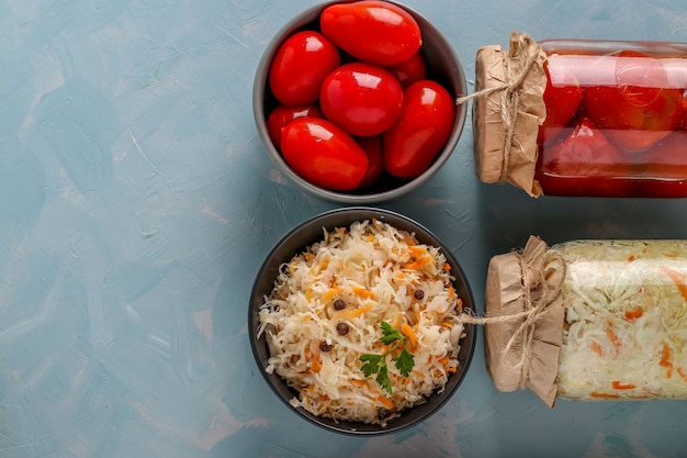 Crauti fatti in casa e pomodori salati in ciotole e vasetti di vetro su sfondo azzurro, concetto di verdure fermentate, vista dall'alto