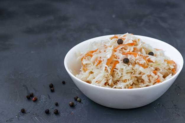 Crauti fatti in casa con carote in una ciotola su uno sfondo scuro, cibo fermentato, chiusura, spazio copia