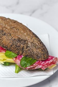 Panino con salsiccia fatta in casa con lattuga e formaggio con pane ai semi. porta via. consegna di cibo