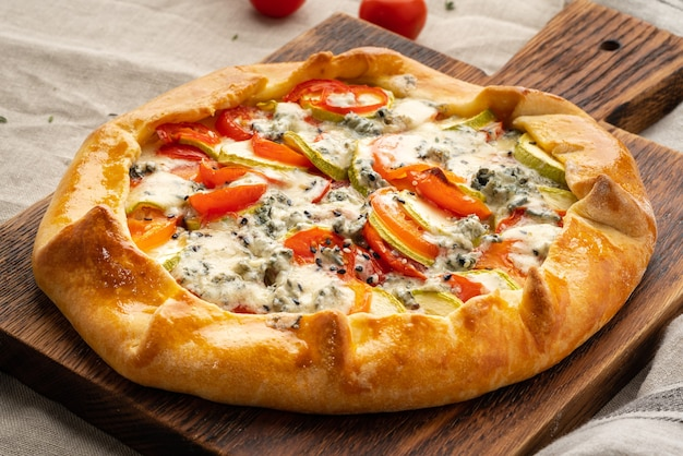 Galette salata fatta in casa con verdure, torta di grano con pomodorini, zucchine, gorgonzola. crostata rustica in crosta su tovaglia tessile di lino scuro.