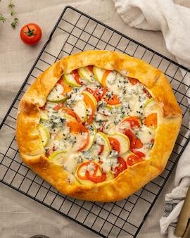 Galette salata fatta in casa con verdure, torta di grano con pomodorini, zucchine, gorgonzola. crostata rustica in crosta su griglia su tovaglia di lino scuro.