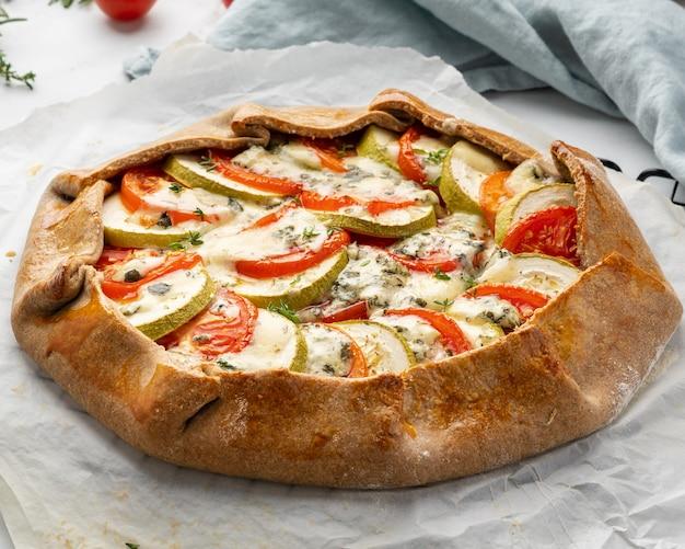 Galette salata fatta in casa con verdure, torta integrale con pomodori, zucchine, gorgonzola. crostata rustica in crosta su tovaglia tessile di lino scuro. vista laterale