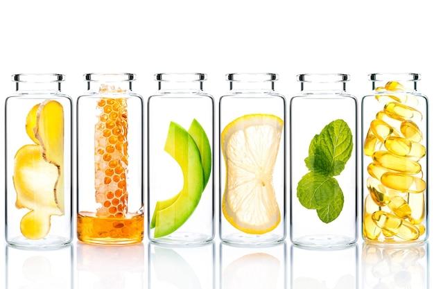 Scrub fatti in casa con ingredienti naturali in bottiglie di vetro isolare su sfondo bianco.