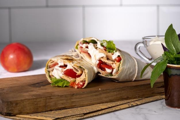 Shawarma fatto in casa o burrito o involtino di pollo con verdure e salsa