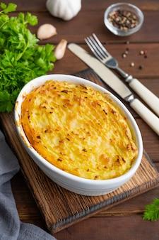 Torta casalinga del pastore nella casseruola su un fondo di legno scuro. piatto tradizionale britannico con carne macinata e purè di patate.
