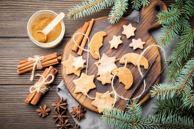 Zucchero a forma di stella di pasta frolla fatta in casa con zucchero in polvere e ramo di albero in forma su legno marrone