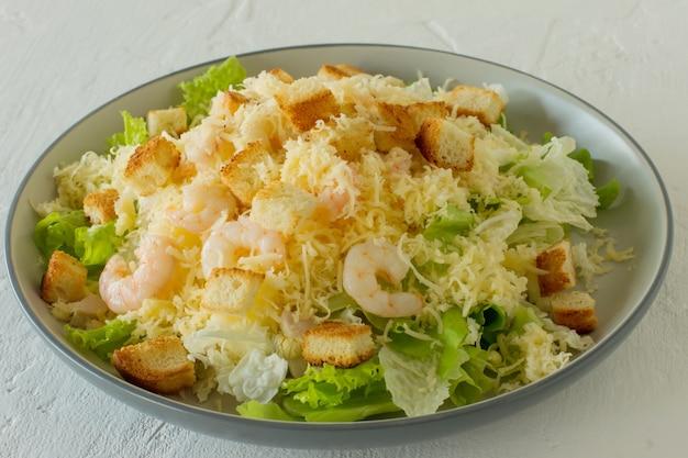 Insalata caesar di gamberi fatti in casa con parmigiano, salsa e crostini di pane su uno sfondo bianco.