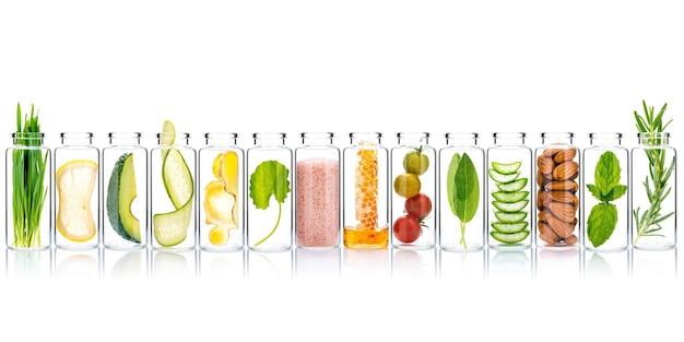 Cura della pelle fatta in casa e scrub per il corpo con ingredienti naturali in bottiglie di vetro isolare su sfondo bianco.