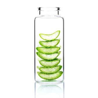 Cura della pelle fatta in casa con fetta di aloe vera in una bottiglia di vetro isolata su bianco.
