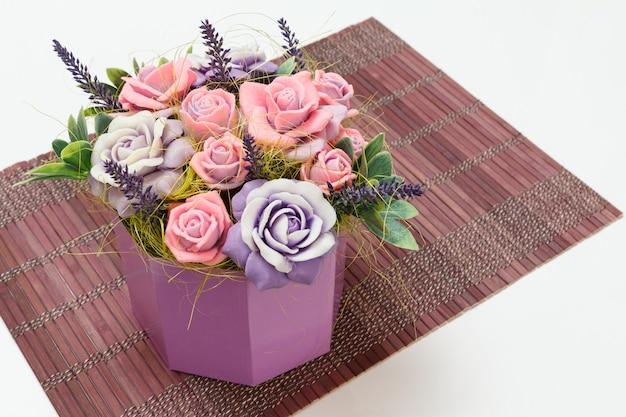 Sapone fatto in casa a forma di rose come regalo sul tovagliolo di bambù. vista dall'alto.
