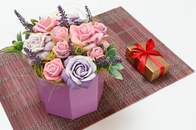 Sapone fatto in casa a forma di rose e una confezione regalo sul tovagliolo di bambù. vista dall'alto.