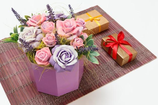 Sapone fatto in casa a forma di rose e scatole regalo sul tovagliolo di bambù