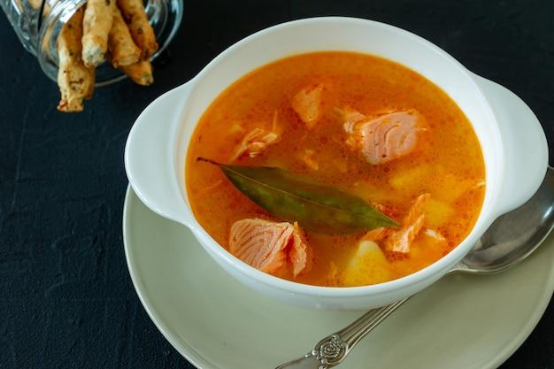 Zuppa fatta in casa con salmone con grissini sul retro dello sfondo di cemento.