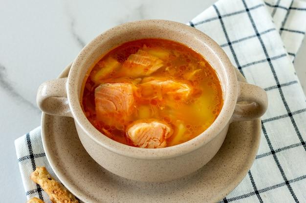 Zuppa fatta in casa con salmone con grissini su fondo marmo.