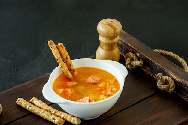 Zuppa fatta in casa con salmone con grissini su vassoio in legno.