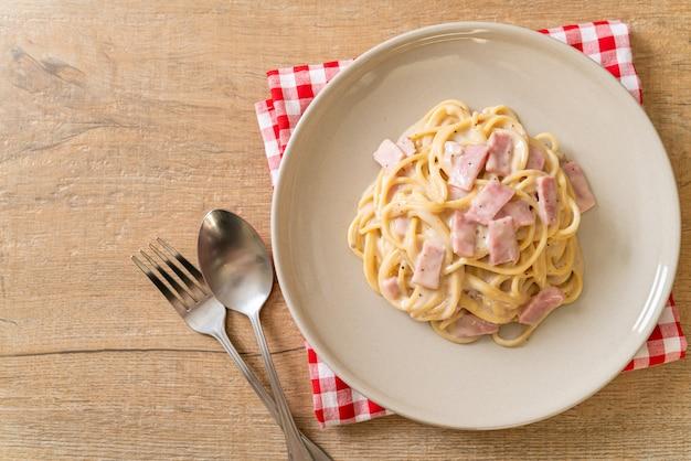 Spaghetti fatti in casa con salsa di panna bianca al prosciutto