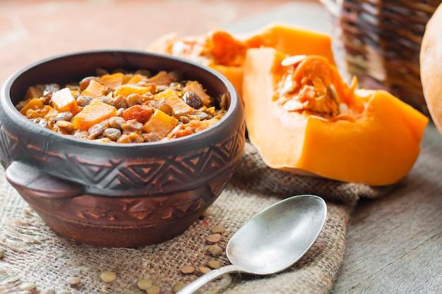 Curry piccante fatto in casa con lenticchie verdi, zucca e uvetta in una ciotola di ceramica rustica
