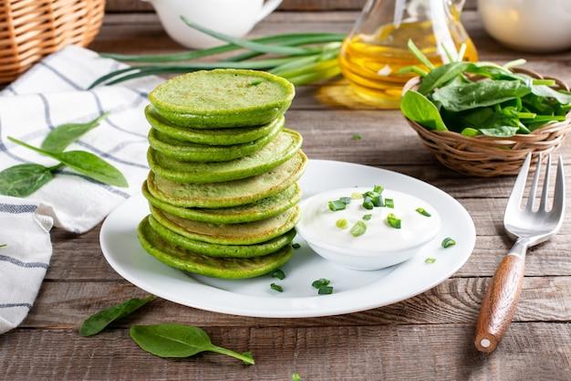 Frittelle di spinaci fatte in casa con panna acida su un tavolo di legno