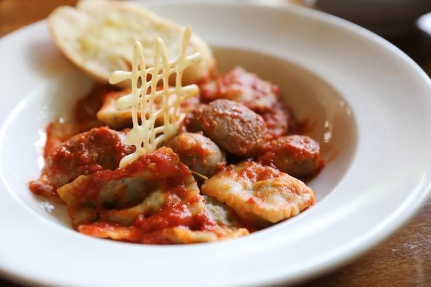 Pasta fatta in casa ravioli di spinaci con salsiccia in salsa di pomodoro su uno sfondo di legno, cibo tradizionale italiano