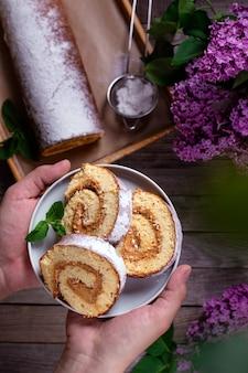 Rotolo di pan di spagna fatto in casa con crema su un piatto in mani su uno sfondo di un tavolo in legno con fiori primaverili