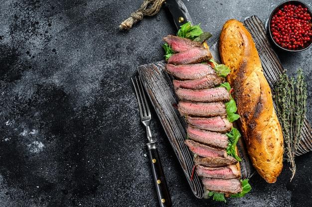 Panino bistecca fatto in casa con roast beef a fette, rucola e formaggio. sfondo nero. vista dall'alto. copia spazio.
