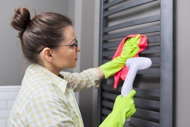 Pulizia a vapore fatta in casa in bagno. donna che pulisce scaldasalviette, usando la macchina a vapore