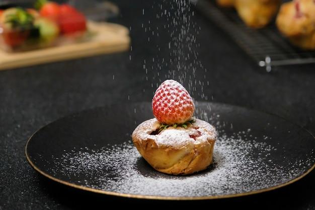 Torta di fragole fatta in casa guarnita con zucchero a velo. cibo dolce. dessert dolce. dessert perfetto stagione estiva servito sul piatto.