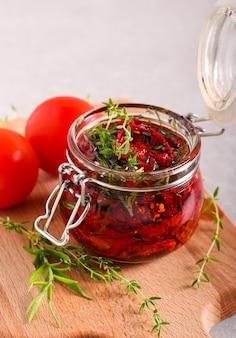 Pomodori secchi fatti in casa con olio d'oliva, erbe aromatiche e spezie in un barattolo