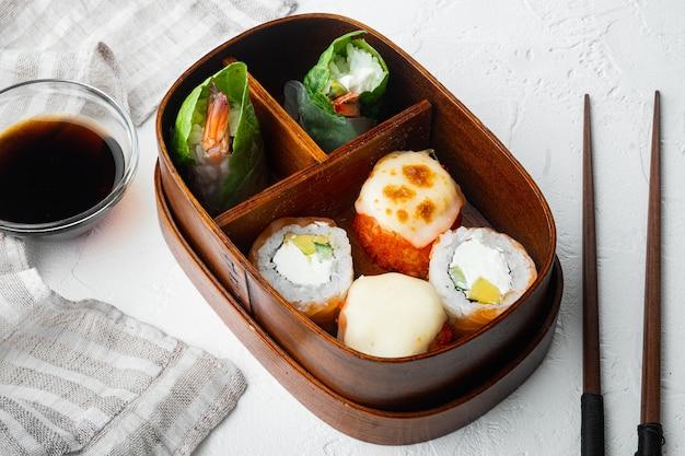 In casa sushi bento box con sushi rolls impostato, su pietra bianca