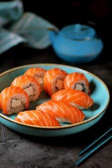 Rotoli di sushi fatti in casa philadelphia e nigiri in un piatto blu su una superficie nera.