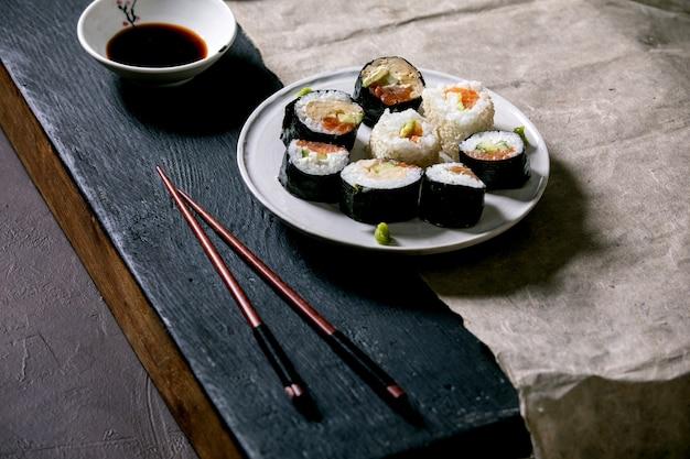 Rotoli di sushi fatti in casa con salmone, frittata giapponese, avacado, wasabi e salsa di soia con bacchette di legno su carta grigia su tavolo di legno nero. cena in stile giapponese