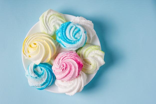 Meringa colorata dolce fatta in casa su fondo blu. dolce.
