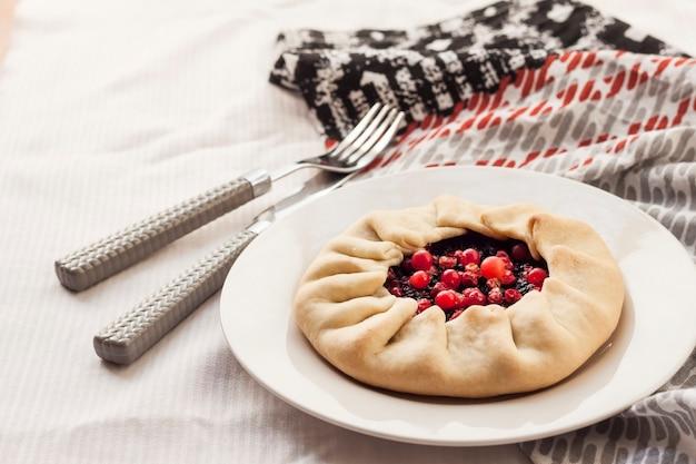 Galette dolce fatta in casa con bacche di sambuco e mirtilli rossi su un piatto