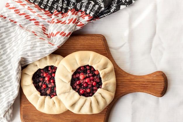 Galette dolce fatta in casa con bacche di sambuco e mirtilli rossi su una tavola di legno vista dall'alto piatta