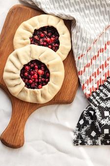 Galette dolce fatta in casa con bacche di sambuco e mirtilli rossi su una tavola di legno
