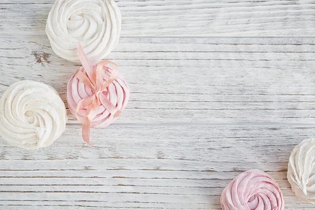 Marshmallow rosa e bianco dolce fatto in casa - zephyr su un tavolo in legno chiaro.
