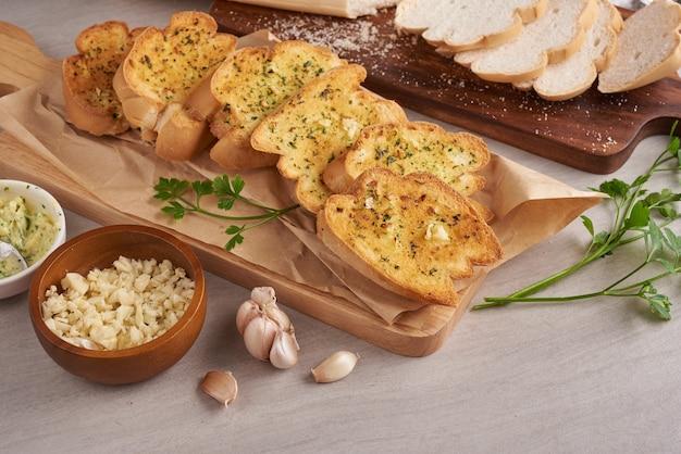 Gustoso pane fatto in casa con aglio, formaggio ed erbe aromatiche sul tavolo della cucina.