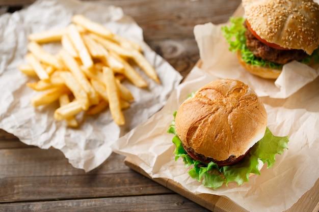 Gustosi hamburger fatti in casa e patatine fritte sul tavolo di legno
