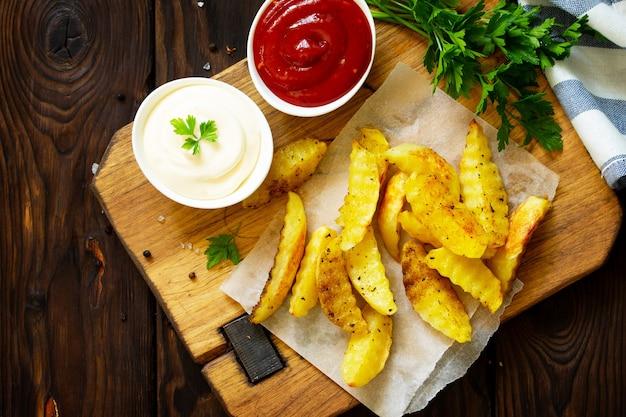 Gustose patatine fritte fatte in casa sul tagliere con maionese vista dall'alto