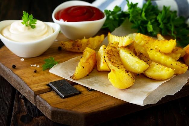 Gustose patatine fritte fatte in casa sul tagliere con maionese e ketchup