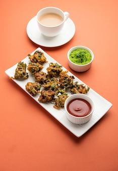 Gustosi palak pakoda o pakora fatti in casa noti come spinaci firtters, serviti con ketchup. spuntino preferito per l'ora del tè dall'india