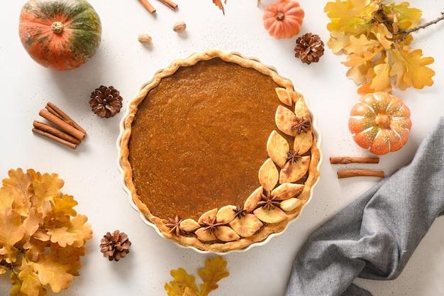 Gustosa torta di zucca fatta in casa con decorazioni autunnali e foglie per il giorno del ringraziamento su bianco