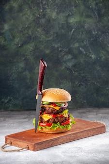 Panino gustoso fatto in casa e forchetta rossa su tagliere di legno su superficie sfocata