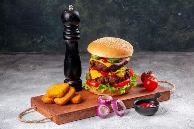 Panino gustoso fatto in casa e pomodori pepite di pollo cipolle pepe su tagliere di legno ketchup su superficie sfocata